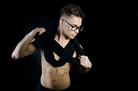 Sexual clever guy with glasses. Handsome young guy. Portrait. Beauty and care. Black background.