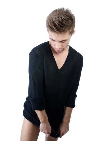 Sexy man undressing. White background. Attractive young guy in black clothes. Isolated. Stock Photo