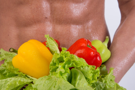 Sport and diet. Attractive man with muscular body. Athletic guy and vegetables. Healthy eating