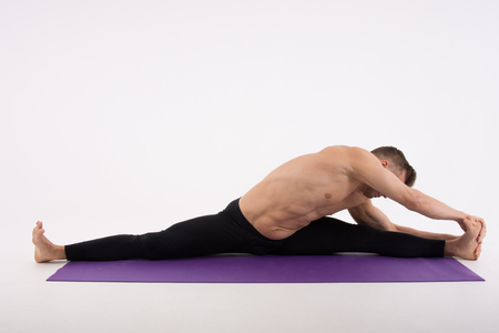 Young handsome man and yoga. Training and relaxation. Healthy lifestyle. Stretching