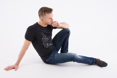 Young handsome man is resting. The sexy guy is sitting on the floor. Muscular and sexy. Gray background 版權商用圖片 - 103782751