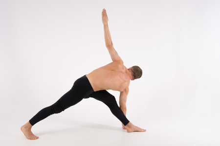 Young handsome man and exercises. Training and relaxation. Healthy lifestyle. Stretching and warm-up