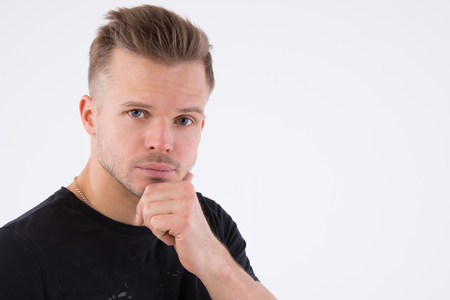 Young handsome man is thinking. The guy in studio. Muscular and sexy. Gray background