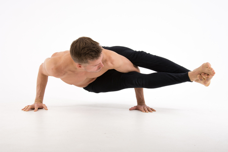 Young handsome man and exercises. Training and relaxation. Healthy lifestyle. Balance and equilibrium