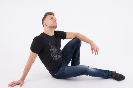 Young handsome man is resting. The sexy guy is sitting on the floor. Muscular and sexy. Gray background