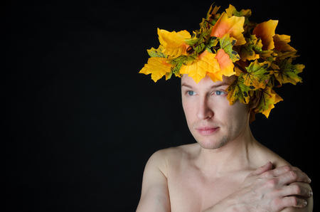 Man in a wreath of maple leaves. Autumn mood. Black background