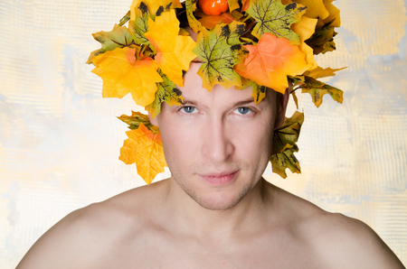 Man in a wreath of maple leaves. Autumn mood