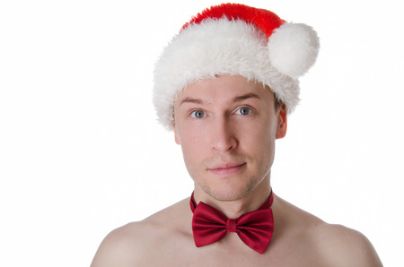 Young sexy Santa in hat and bow-tie. Holiday and gifts. New Year and Christmas. Naked sexy guy 版權商用圖片
