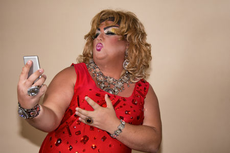 Funny travesty actor. Drag queen and phone. Selfie. Fat man and make-up