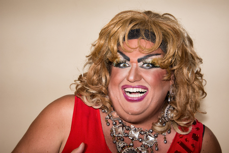 Funny travesty actor. Drag queen in red. Feelings and emotions. Fat man and make-up. Joy