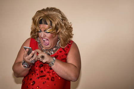 Funny travesty actor. Drag queen and phone. Feelings and emotions. Fat man and make-up 版權商用圖片 - 105788820