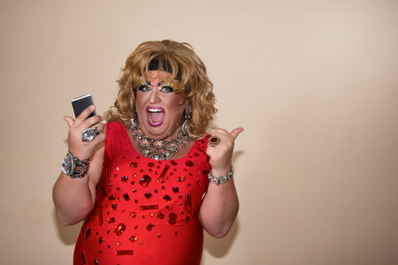 Funny travesty actor. Drag queen and phone. Feelings and emotions. Fat man and make-up 写真素材 - 105788822