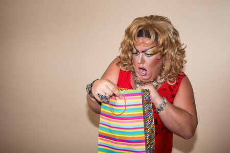 Funny travesty actor. Drag queen and gift. Fat man and make-up
