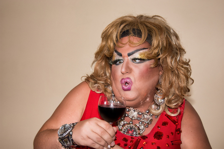 Funny travesty actor. Drag queen and red wine. Feelings and emotions Stock fotó