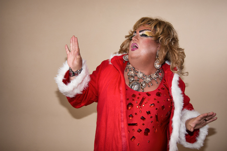 Funny travesty actor. Drag queen in santa costume. Fat man and make-up.