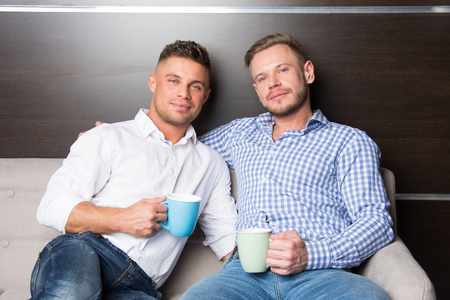 Love and relationships. Two happy guys together on couch 版權商用圖片