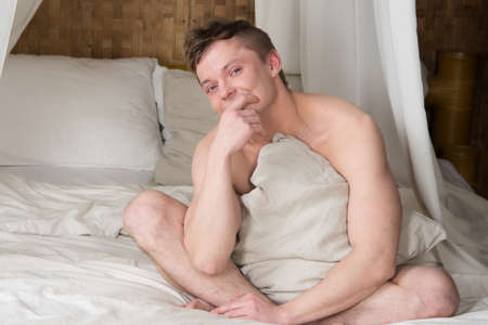 Adult man resting in bed. Sexy guy.