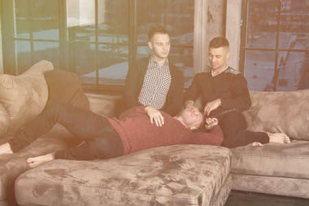 Three attractive guys relaxing at home. 写真素材