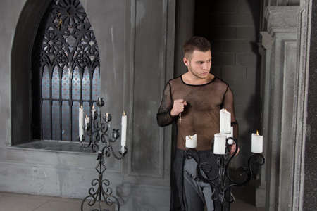 Prayer and sins. Young attractive guy in the church.