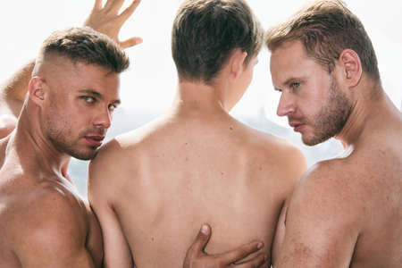 Three young attractive guys. Love and relationships. Imagens