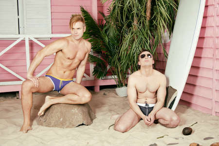 Vacation and holidays at sea. Attractive gay family couple relaxing on the beach. 免版税图像