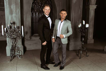 Young happy couple getting married in church. Love and romance. Handsome men in suits.