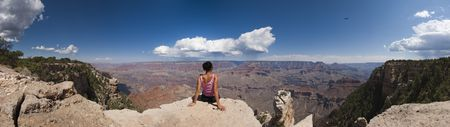 Loneliness women seat down on the rock of Grand Canyon Arizona USA panoramic Stock Photo