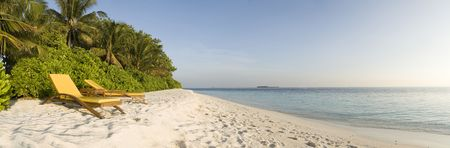 Relax chair on white sand beach of Ihuru Island Maldives in Malé North atoll and blue lagoon panoramic view Stock Photo