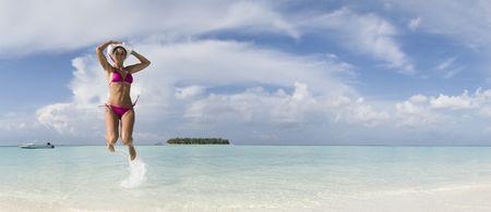 Women jump in blue lagoon of Ihuru Island Maldives Malé North atoll panoramic
