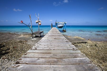 White and blue fishermens boat on blue lagoon and wood pontoon of a paradise island