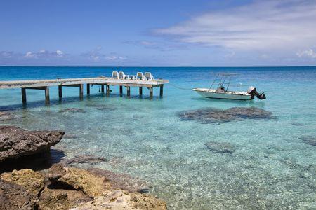 moorea: White funboat on blue lagoon and wood pontoon Stock Photo