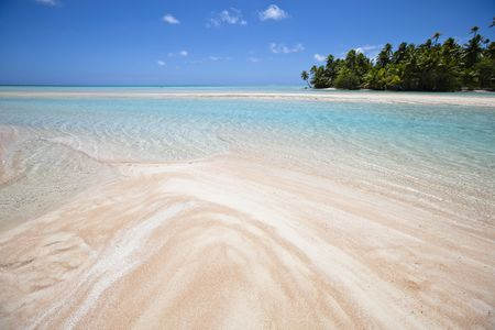 White and rose sand beach front of blue lagoon and tropical island photo