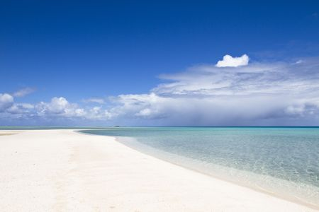 Desert white sand beach front of a turquoise lagoon photo