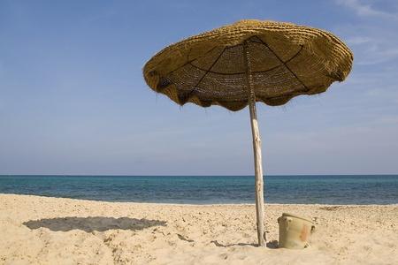 Un ombrella sur le front de plage de sable de mer et le bleu ciel horizon