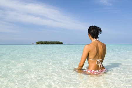 A woman suntanning on a white sand beach of a tropical island front of a blue lagoon in Maldives