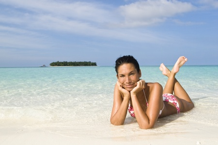 suntanning: A woman suntanning on a white sand beach of a tropical island front of a blue lagoon in Maldives