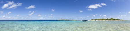 Boat on blue lagoon front of a paradise island panoramic view