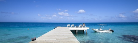martinique: Boat on blue lagoon with a woman seat on chair of a pontoon in paradise island