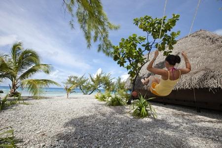 Femme sur swing devant du lagon bleu dans une plage de paradis pr�s de bungalow