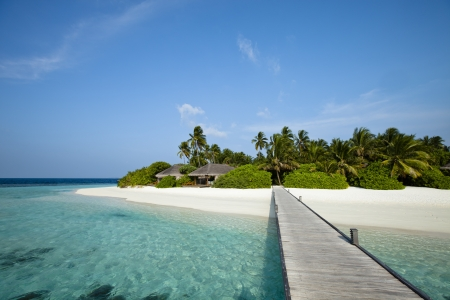 A wood pontoon access to paradise beach of a tropical island photo