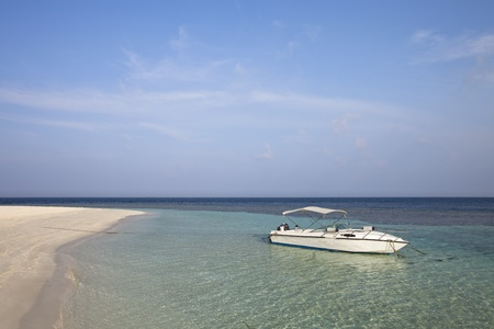 A recreational white boat on lagoon front beach of paradise island photo