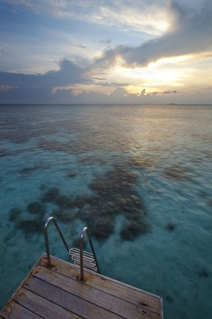 french polynesia: In paradise island, wood pontoon and scale front of a blue lagoon and sunset Stock Photo