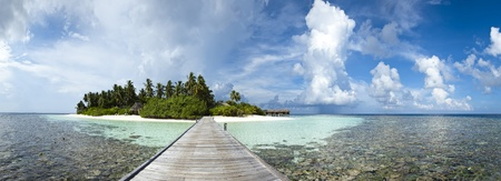 A panoramic view of a paradise island with wood pontoon, blue lagoon and palmtree Stock Photo
