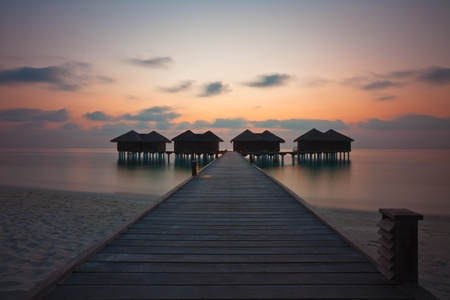 Watervilla of a luxury hotel front of lagoon at sunset