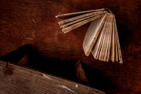books on a wooden surface: Stool and book on the board in brown tones.