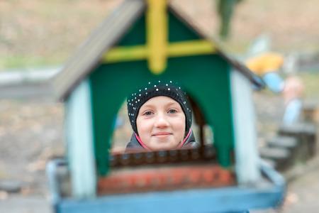looking through: Young girl looking through the bird feeder window. Stock Photo