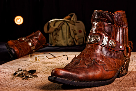 carelessness: Carelessly thrown on the wooden floor male accessories: cowboy shoes, bag and others.