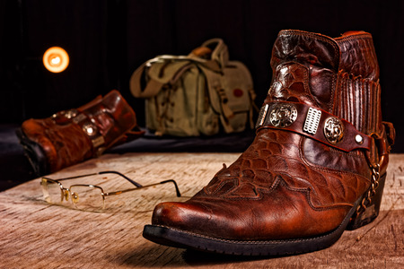 the thrown: Carelessly thrown on the wooden floor male accessories: cowboy shoes, bag and others.