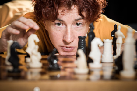 ordinary woman: Ordinary woman leaning over a chessboard with the set pieces.