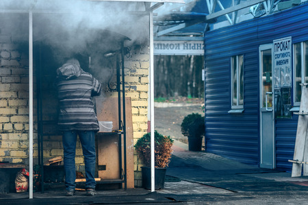 roasting: Moscow, Russia - November 14, 2015: man roasting meat on the BBQ in the city park. Editorial